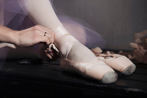 Crop ballet dancer tying pointe shoes