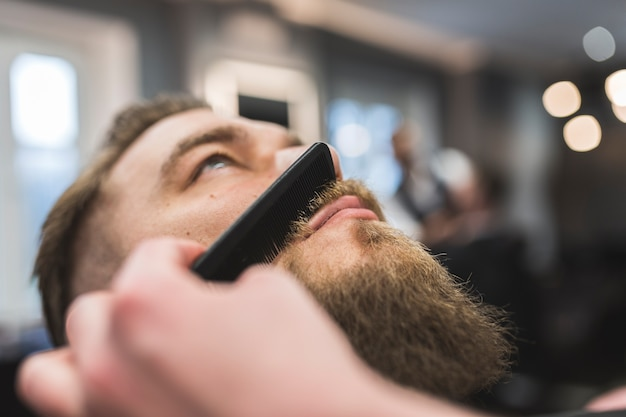 Crop barber combing moustache of client