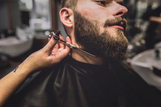 Crop barber cutting beard