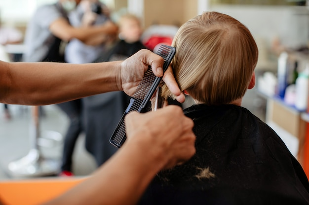 Crop barber doing haircut to little boy