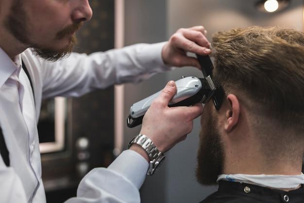Crop barber shaving temples of man