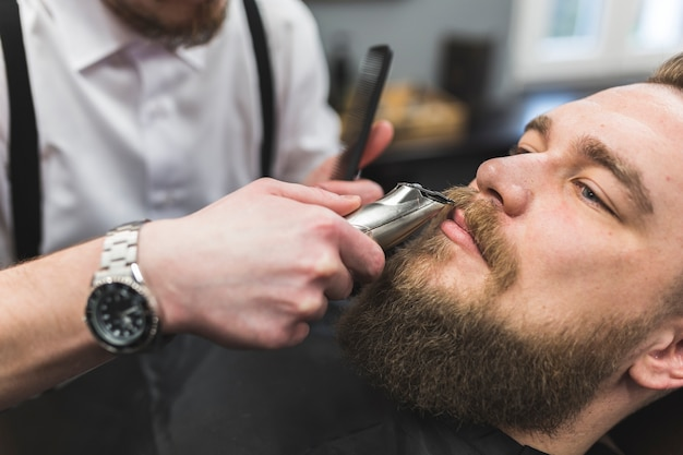 Crop barber trimming moustache of client