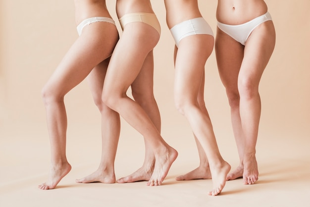 Crop barefoot female figures in underwear standing behind each other