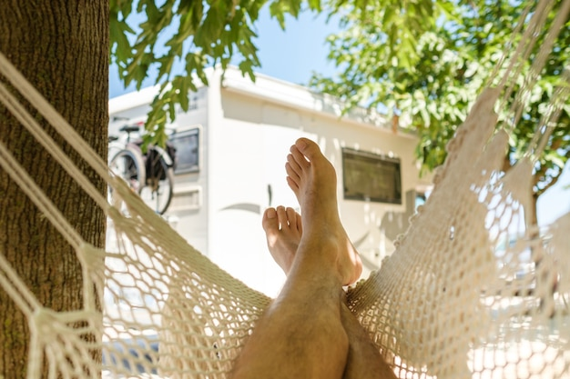 Crop barefoot man relaxing in hammock near tree trunk and caravan on sunny weekend day in summer