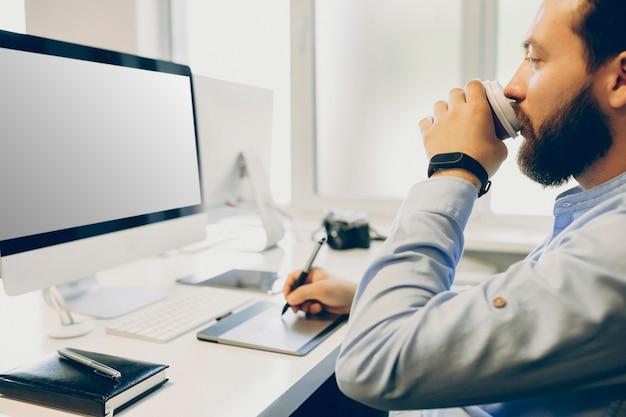 사무실에서 디자인 프로젝트를 진행하는 동안 컵에서 뜨거운 음료를 마시고 드로잉 태블릿을 사용하여 수염 난 남자를 자르십시오.