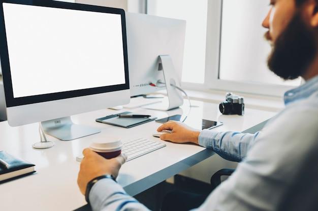 オフィスで働いている間、熱い飲み物のカップを保持し、空白の画面でコンピューターを閲覧しているひげを生やした男を作物