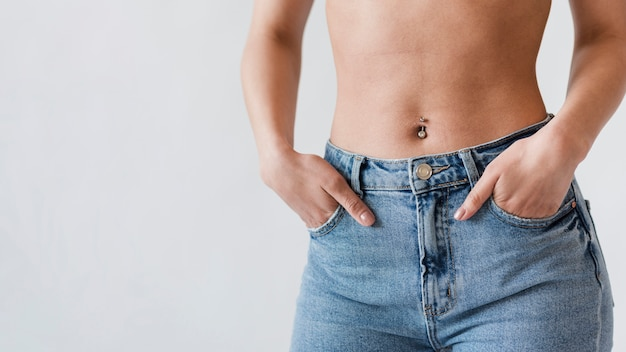 Crop of belly of woman in denim