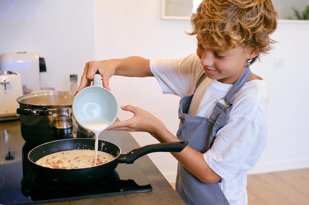 ストーブの鍋にミルククリームを注ぐ作物の少年