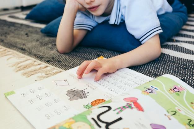 Crop boy reading textbook on floor