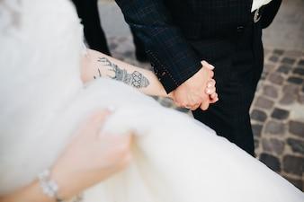 Crop bride and groom holding hands