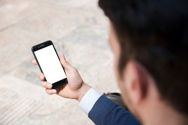 Crop businessman holding smartphone on street