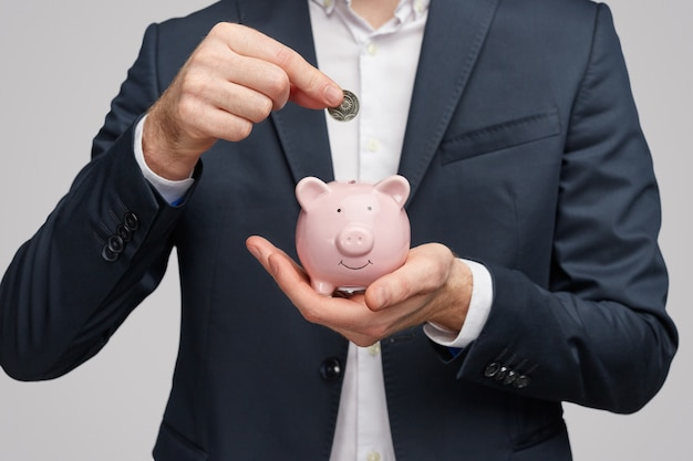 Crop businessman inserting coin in piggy bank