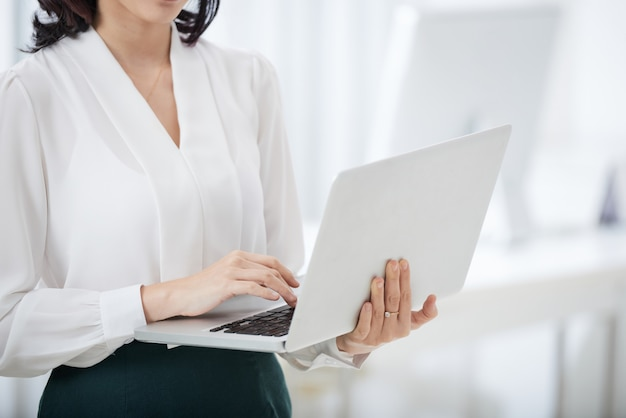 Crop businesswoman using laptop