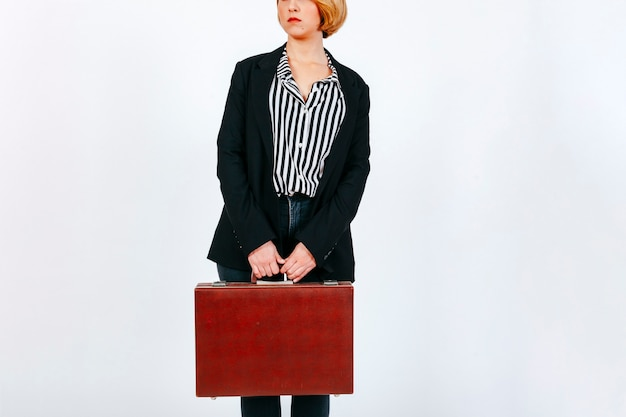 Crop businesswoman with suitcase
