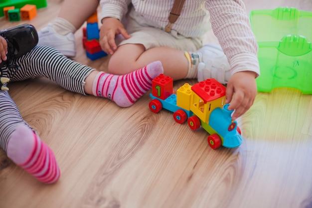 Coltivi i bambini sul pavimento con i giocattoli