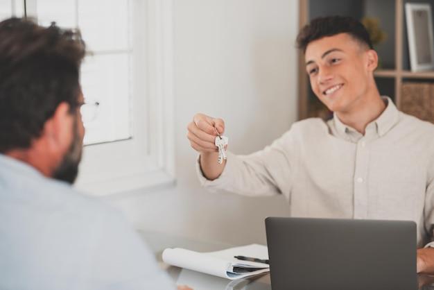 不動産業者の作物のクローズアップは、代理店から最初の家を購入する男性の購入者または賃貸人に鍵を与えます。不動産業者またはブローカーは、男性のテナントに住宅またはアパートの購入を祝福します。所有権、賃貸コンセプト。