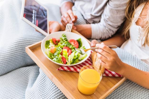 Crop couple enjoying salad while watching tv series