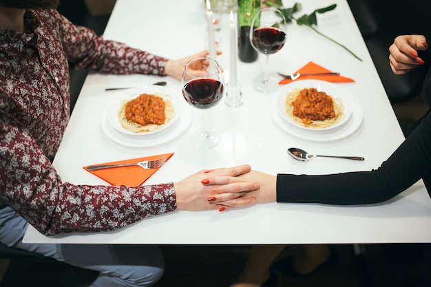 Crop couple holding hands on table