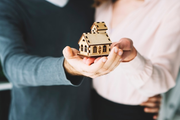 Crop couple holding toy house
