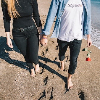 Crop couple in love walking on beach