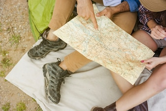 Crop couple reading map