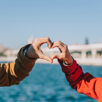 Crop couple showing heart with hands