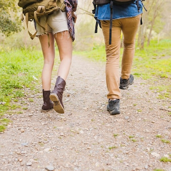Crop couple walking along path