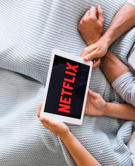 Crop couple watching tv series in bed
