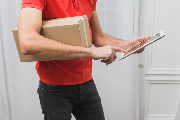 Ritaglia il corriere con pacco e tablet
