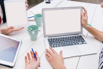 Crop coworkers using laptop