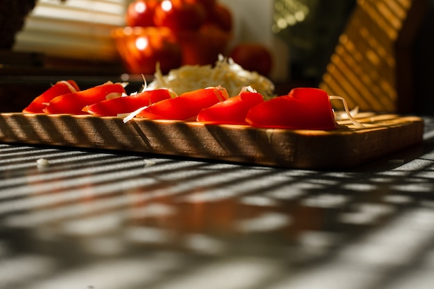 Crop of cut tomatoes and grated cheese.