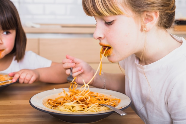 Crop cute child eating pasta