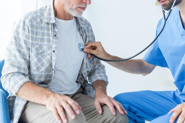 Crop doctor examining lungs of elderly patient
