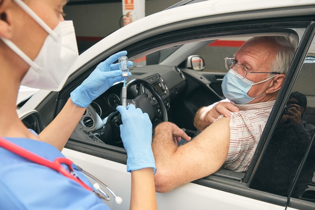 Crop doctor filling syringe with vaccine against driver in auto