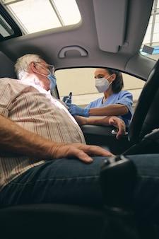 Crop doctor vaccinating senior driver in automobile