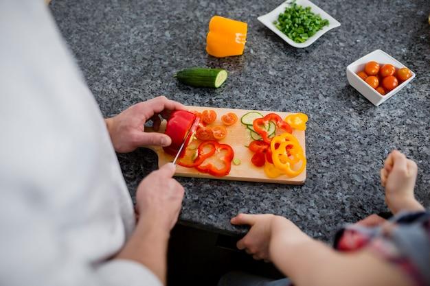 作物の父と娘の野菜を切る