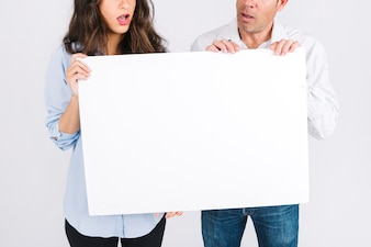 Crop father and daughter holding blank poster