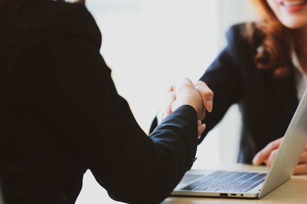 사무실에서 회의를 하는 동안 계약을 체결한 후 노트북을 통해 파트너와 악수하는 작물 여성 기업가. 비즈니스 성공과 협상 개념입니다.