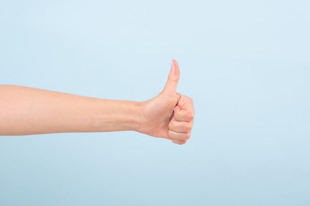 明るいマニキュアで女性の手をトリミングし、親指を立てて無地の光に逆らって承認します