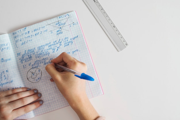 Crop female hands writing in notebook
