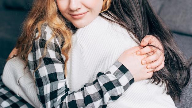 Crop females hugging at home