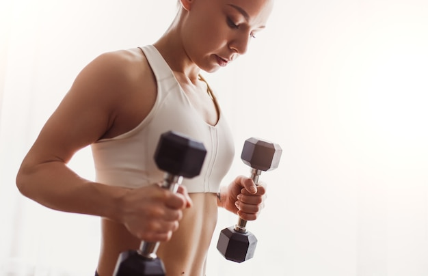 Crop fit female athlete doing exercise with dumbbells during fitness exercise at home