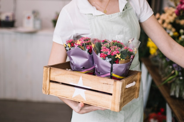 Crop florist carrying flowers in box