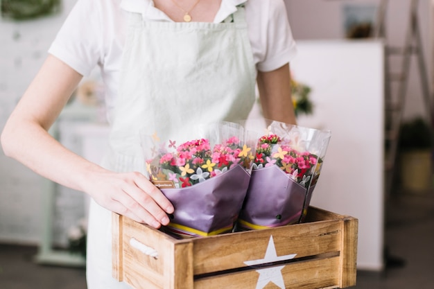 Crop florist putting flowers into box