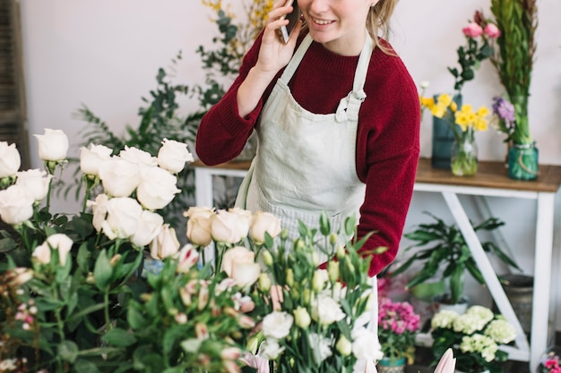 Crop florist speaking on smartphone