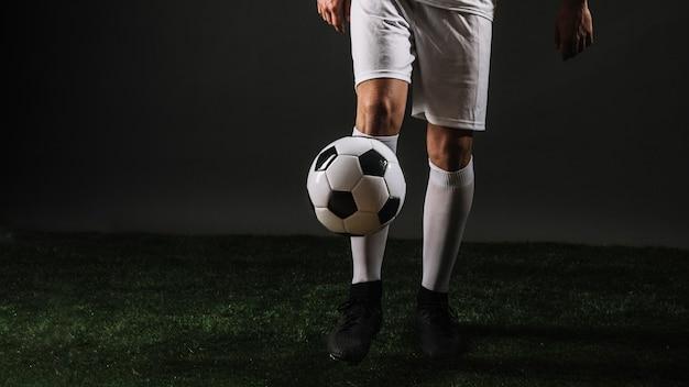 Crop football player juggling ball