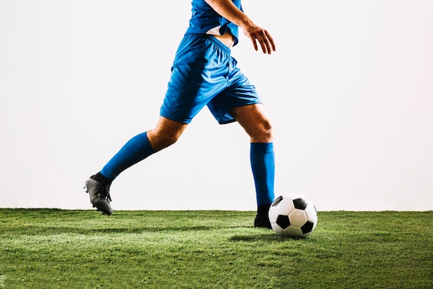 Crop football player shooting ball