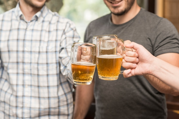 Crop friends clinking mugs in bar