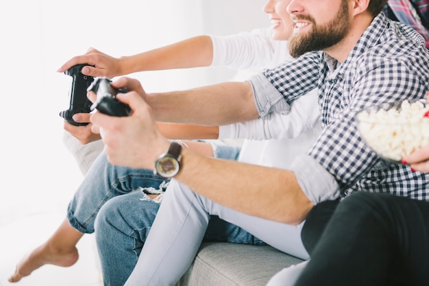 Crop friends playing videogame on sofa