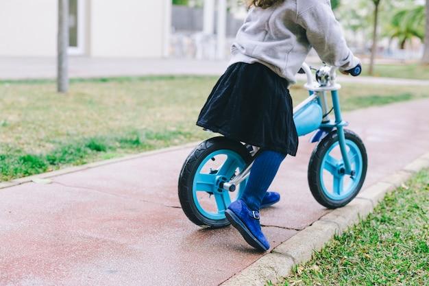 Crop girl riding bicycle